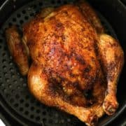 Whole roast chicken sitting in air fryer basket.