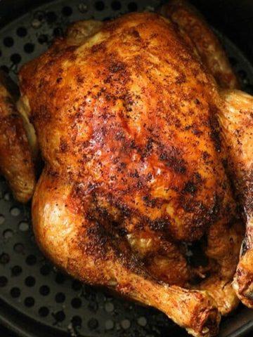 Whole roast chicken sitting in air fryer basket.