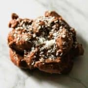 a chocolate covered almond cluster on a marble background