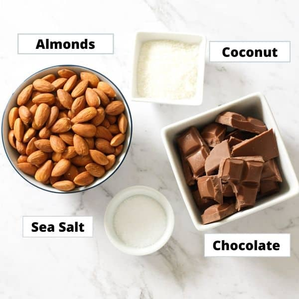 ingredients for chocolate covered almonds on a marble background.