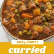 "curried sausages in a big bowl with text overlay ""curried sausages""."