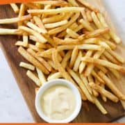 "fries on a wooden board with text overlay ""air fryer french fries""."
