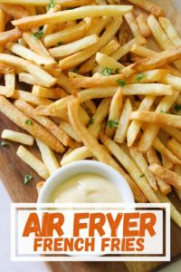 """fries on a wooden board with text overlay """"air fryer french fries""""."""