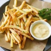 French fries on a grey plate with a bowl of aioli.