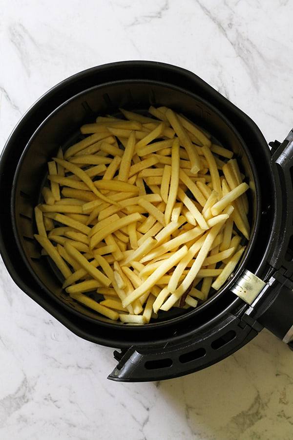 frozen french fries in an air fryer basket.