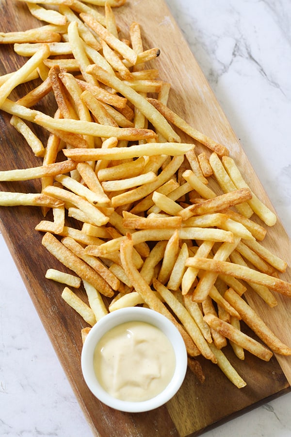 French fries on a wooden serving board.