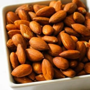 Roasted almonds in a white square serving bowl.