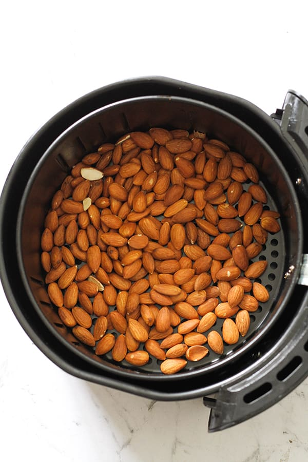 plain almonds in an air fryer basket.