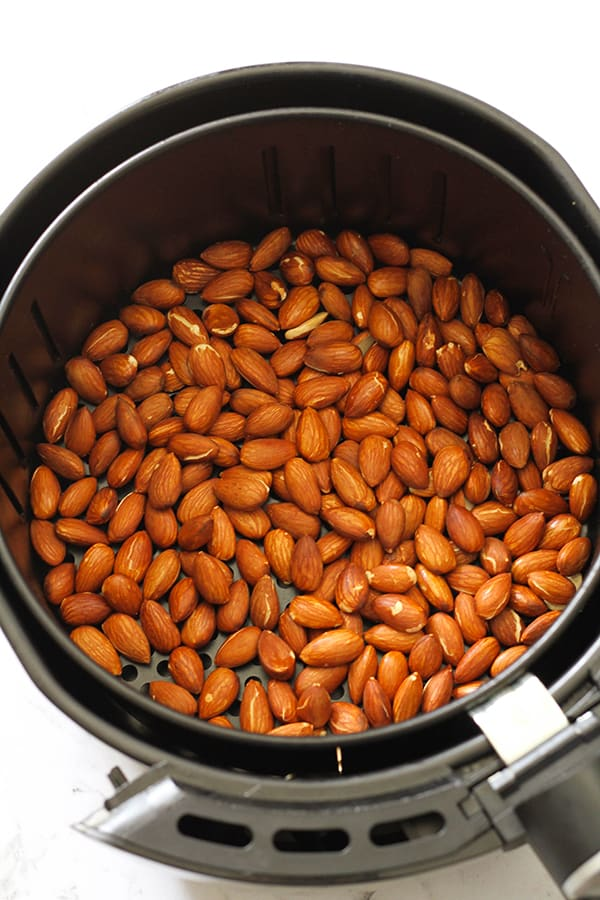 dry roasted almonds in air fryer basket.