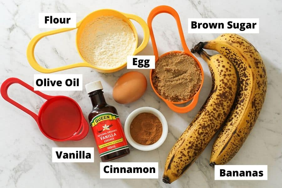 Air Fryer Banana Muffins Ingredients on a white marble background.