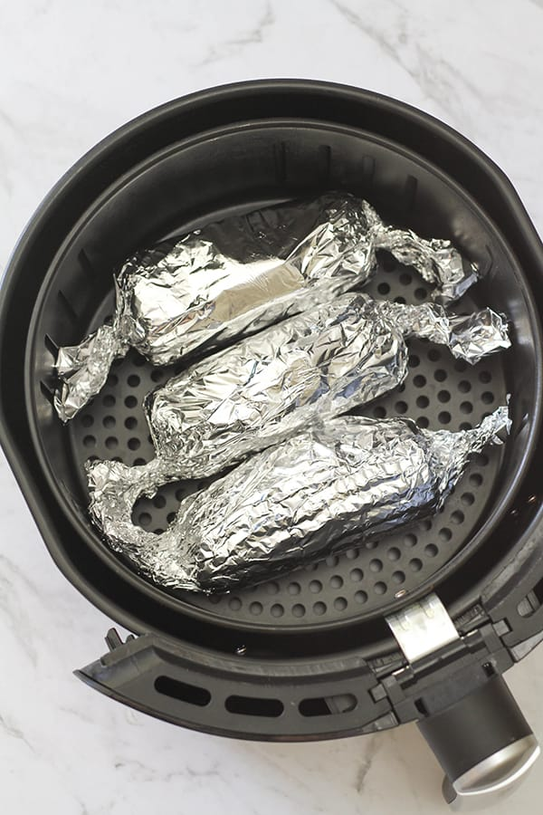 3 ears of corn wrapped in aluminium foil in an air fryer basket.