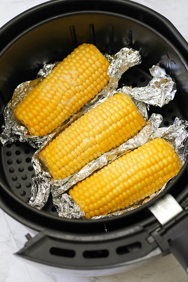 corn ears in an air fryer basket.