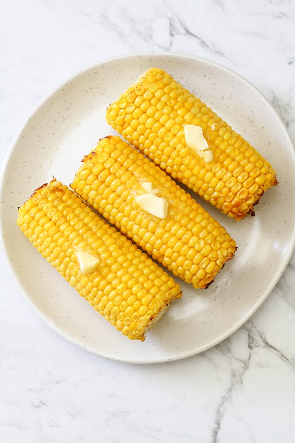 3 corn on the cob on a white plate.