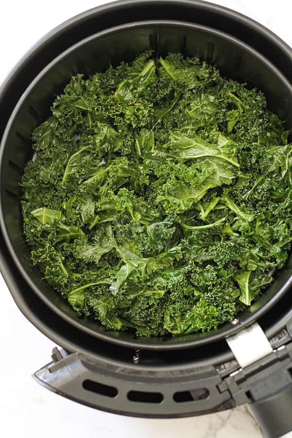 kale leaves in air fryer basket.