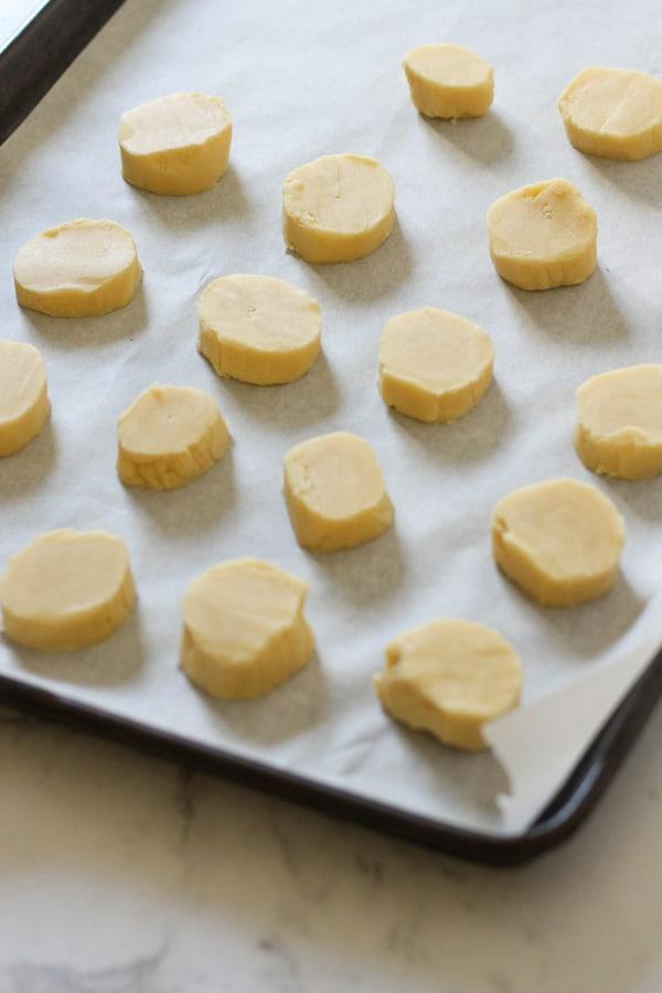shortbread dough rounds on a baking tray.