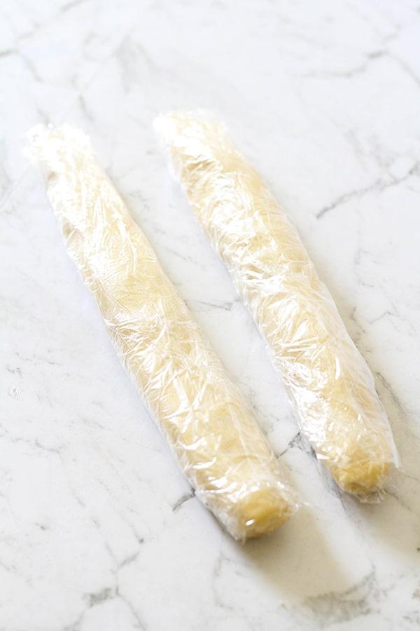 shortbread dough logs wrapped in plastic wrap.