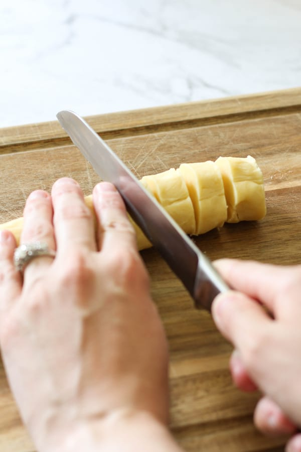 a hand slicing a shortbread dough log into round to be baked.