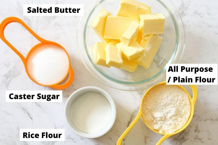 shortbread ingredients laid on a white marble background.