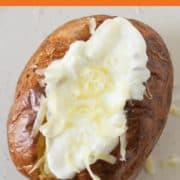 baked potato topped with sour cream and cheese.