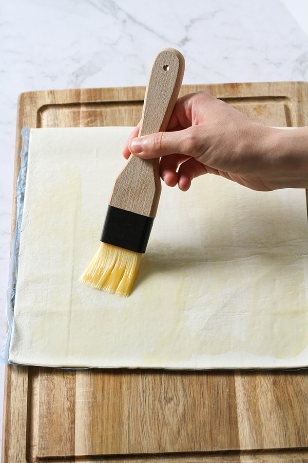 pastry sheet being brushed with butter.