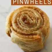 a cinnamon pinwheel on a white marble background.