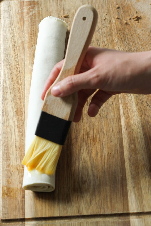 rolled pastry being brushed with eggs.