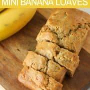 Mini banana loaves on a wooden cutting board.