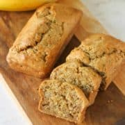 Mini banana loaves on a wooden cutting board.