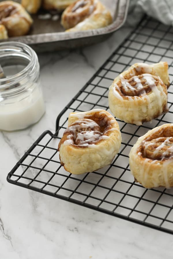 cinnamon rolls on a wire rack.