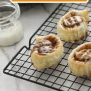 "cinnamon rolls on a wire rack with text overlay ""puff pastry cinnamon rolls""."