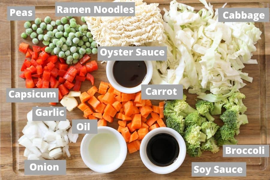 ingredients for vegetable stir fry with noodles on a wooden board.