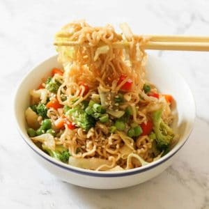 vegetable stir fry with noodles in a white bowl with chopsticks.