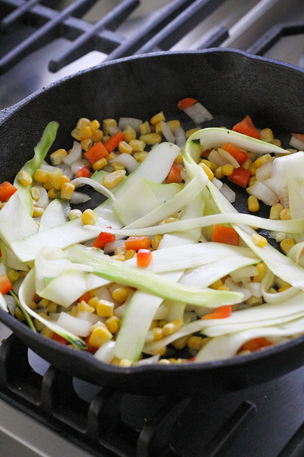 vegetables frying in a cast iron pan.