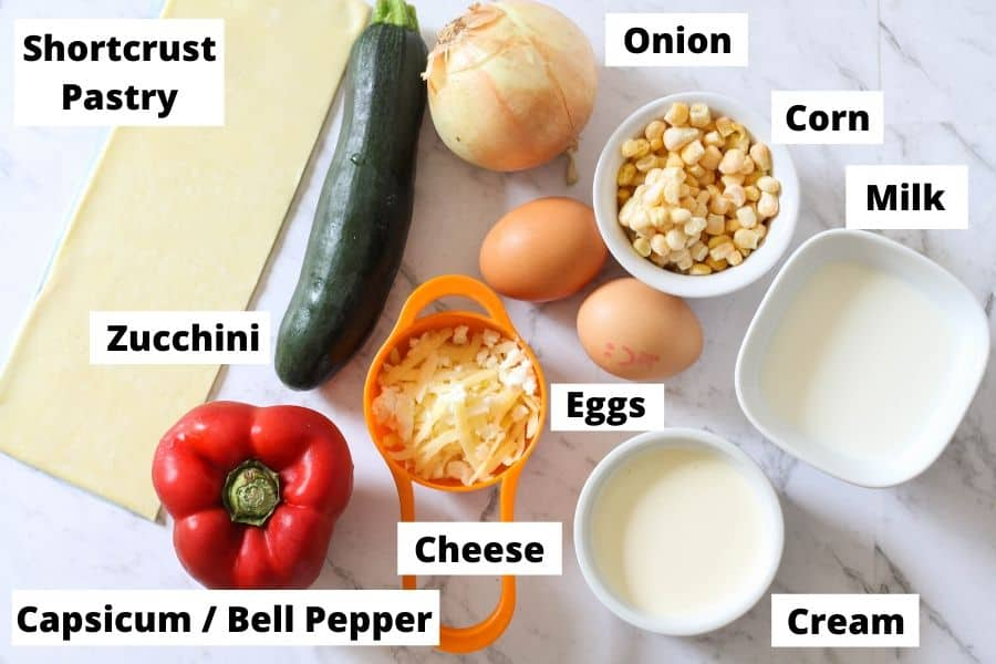ingredients for vegetarian quiche on a white marble background./