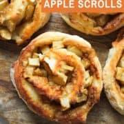 air fryer apple cinnamon rolls on a wooden cutting board.
