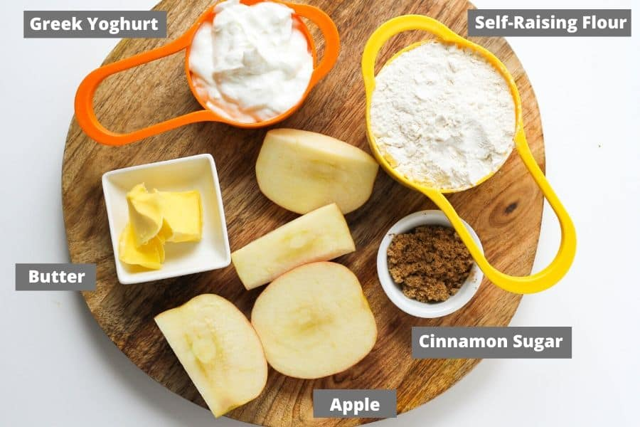 air fryer apple cinnamon roll ingredients on a wooden board.