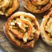 air fryer apple cinnamon rolls on a wooden cutting board.