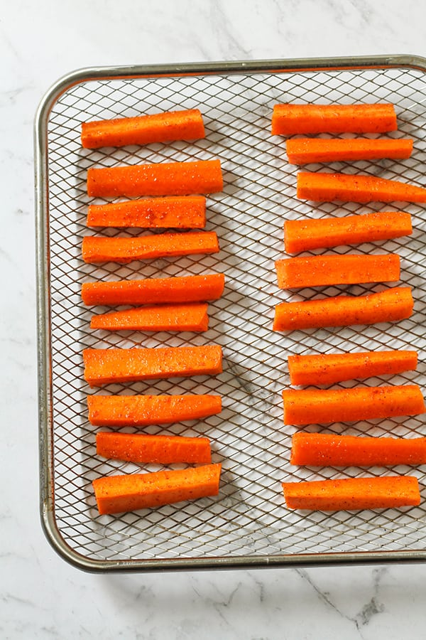 carrot sticks on an air fryer wire tray.