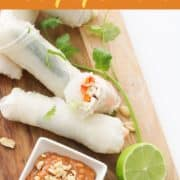 chicken rice paper rolls on a wooden serving board.