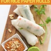 peanut hoisin sauce in a small square white bowl on a wooden board with rice paper rolls.