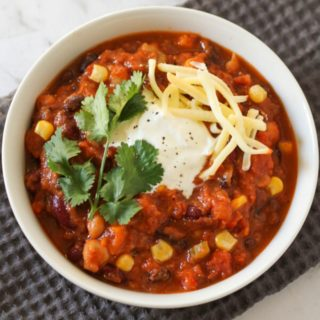 vegetarian three bean chili in a white bowl topped with greek yoghurt, cheese and cilantro.