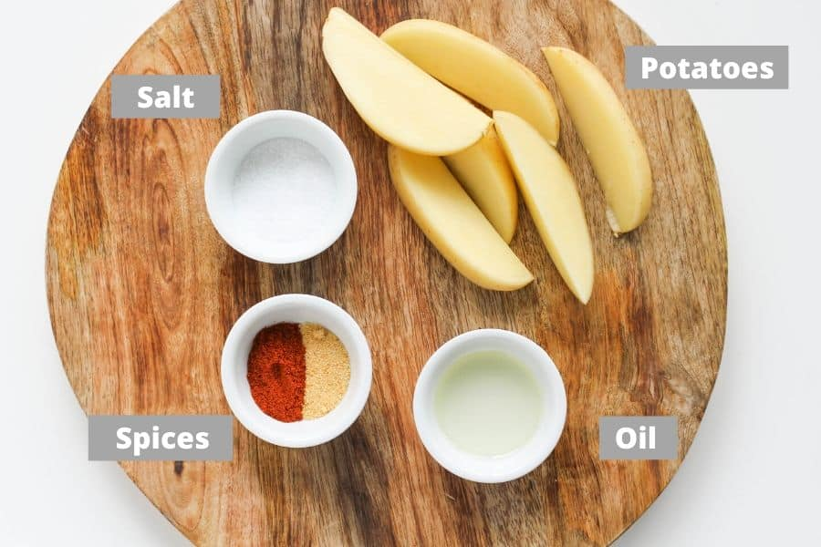 ingredients for potato wedges on a wooden board.