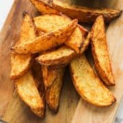 potato wedges on a wooden cutting board.