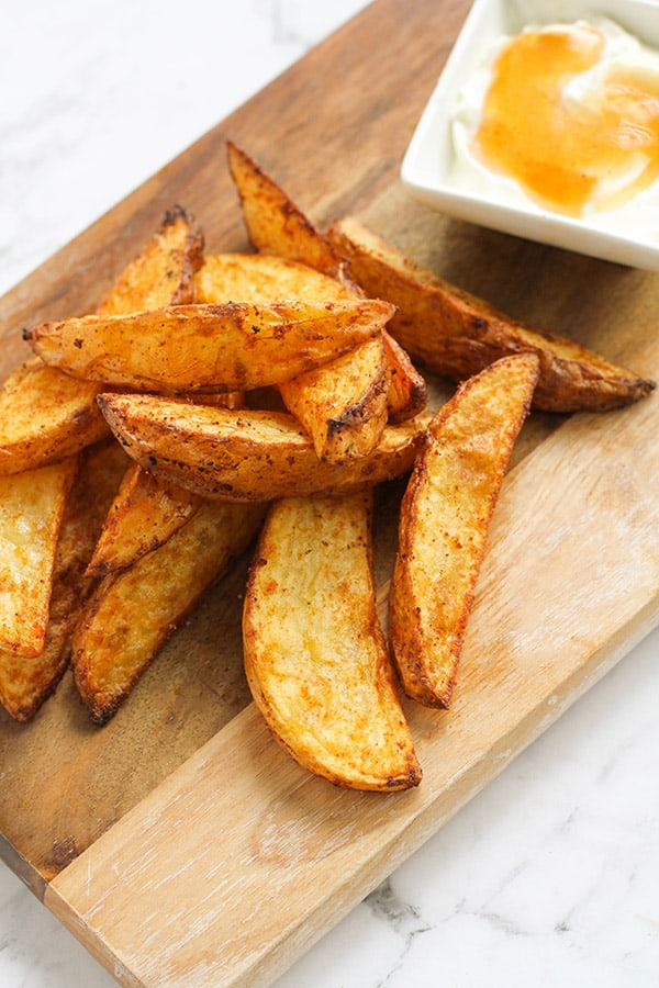 potato wedges and dipping sauce on a wooden cutting board.