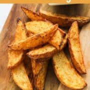 """potato wedges on a wooden board with text overlay """"air fryer crispy potato wedges""""."""