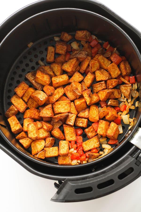 breakfast potatoes in an air fryer basket.