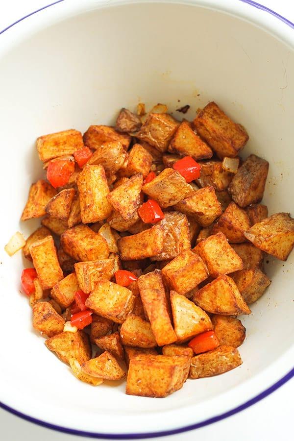 breakfast potatoes in a white bowl.