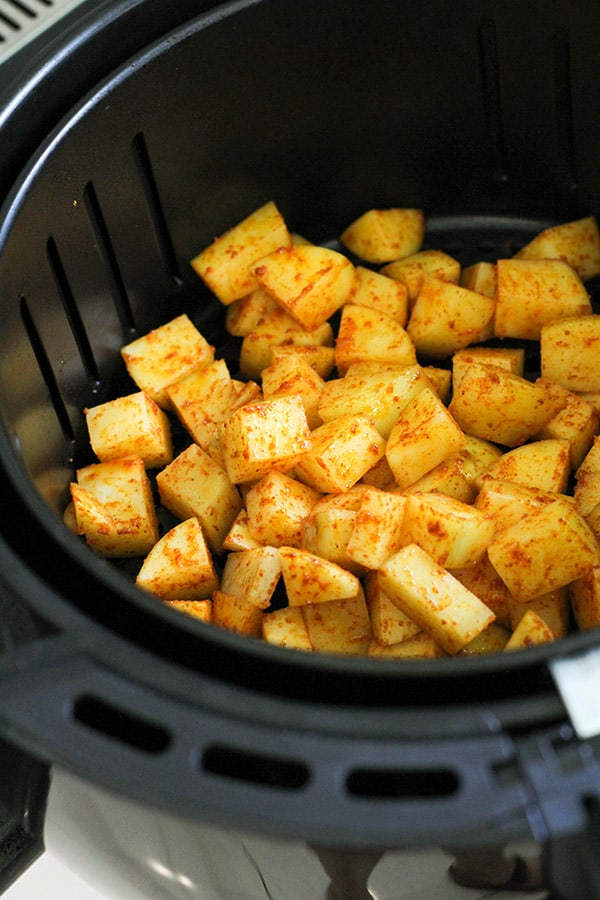 potatoes in an air fryer basket.