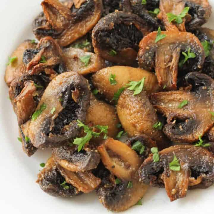 a close up image of air fryer mushrooms covered in parsley.