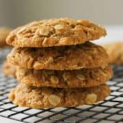 Chewy Anzac biscuits stacked on top of each other on a wire rack.